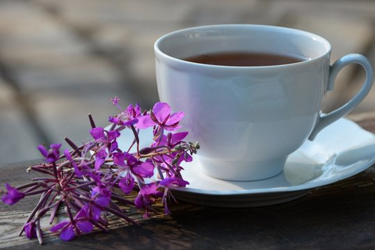 Cup of tea and flowers of fireweed on a saucer on a wooden table close-up.