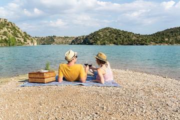 Pareja joven brindando y mirándose el uno al otro durante un romántico picnic cerca de un hermoso lago