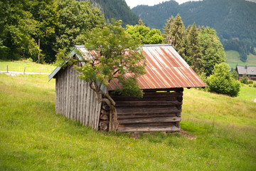 Old wooden bar with rusty roof over the Alps mountain peak