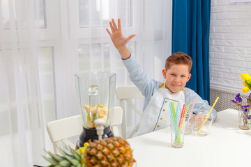The boy is sitting at the table, asks to pour him a drink, hand up.