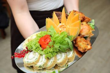 Pięknie udekorowane mięso z kurczaka, warzywa i owoce na tacy trzymanej przez kelnerkę w restauracji.