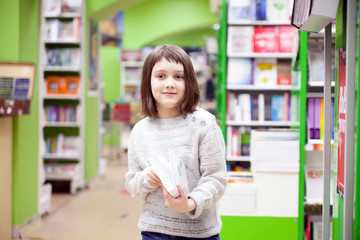 Cute girl  reading  books  at   store