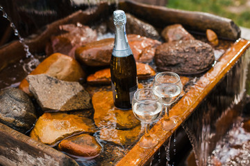 Love, romance, holiday, celebration concept. Bottle and glasses of champagne chilled by waterfall in summer forest on sunset.