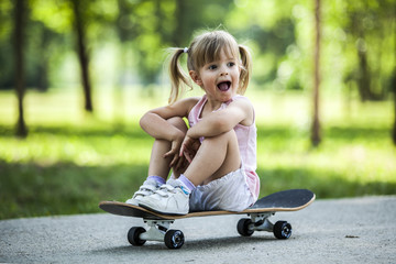 Little blonde girl playing with skateboard in forest park