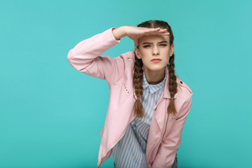 looking too far. portrait of beautiful cute girl standing with makeup and brown pigtail hairstyle in striped light blue shirt pink jacket. indoor, studio shot isolated on blue or green background. Wall mural