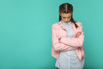 sad upset or depressed portrait of beautiful cute girl standing with makeup and brown pigtail hairstyle in striped blue shirt pink jacket. indoor, studio shot isolated on blue or green background.