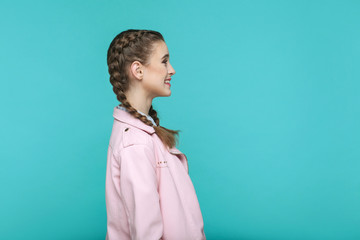 profile side view of happy toothy smiley portrait of beautiful cute girl standing with makeup and brown pigtail hairstyle in pink jacket. indoor, studio shot isolated on blue or green background.