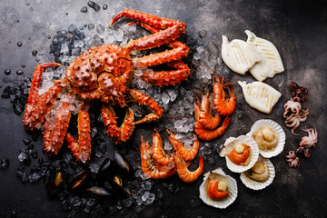 Boiled Seafood on ice - King Crab, Prawn Shrimp, Mussels Clams, Scallops in shells, Octopus mini, Squid on Grill on dark background