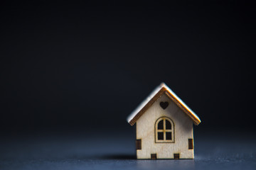 Wooden decorative toy house standing alone on black background. Purchasing or buying a house or rental of property, cosy home and new house for children concept