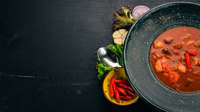 Tomato soup with beef and chili peppers in chervrniy plate. On a wooden table. Top view. Copy space.