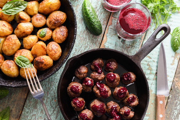 Healthy Nordic cuisine. Fried potatoes, meatballs with berry sauce in cast iron pans and lingonberry drink on rustic blue table