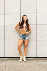 Portrait of athletic young cute woman in denim shorts, pink top and fashion glasses smiling and have good time. Urban style, healthy girl lifestyle and sport concept. Hipster city life.
