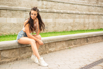 Portrait of athletic young woman in denim shorts, pink top and fashion hair style smiling and have good time in summer city. Urban style, healthy girl lifestyle and sport concept. Hipster city life.