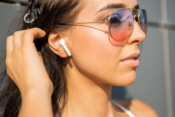 Close up portrait of athletic young cute woman in vogue sport suit correct her wireless sound earpods music headphones. Urban style, healthy girl lifestyle and sport concept. Hipster city life.
