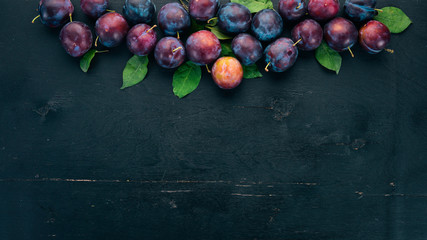 Fresh plums with leaves. Fruits. On a black wooden background. Top view. Free space for your text.