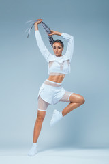 Attractive excited fitness girl dancer in sportwear jumping of joy isolated over gray background