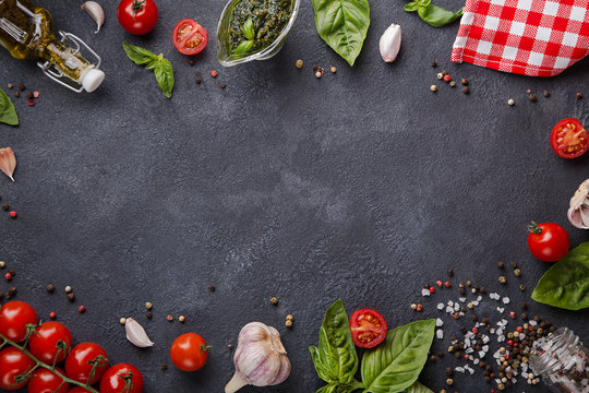 Italian food on dark background with copy space horizontal. Cherry tomatoes, garlic, basil, olive oil, pesto, pepper mix, salt and red napkin