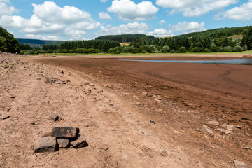 A dried up reservoir showing just dust and rocks during a summer heatwave (Llwyn-On Reservoir)