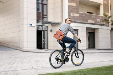 Eco friendly. Happy positive man riding a bicycle while going to work