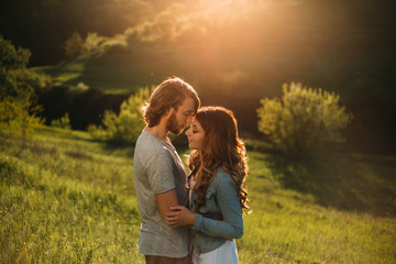 Stylish young couple. Film photo with a light and a sunlight. A guy with a stylish haircut and a red-haired girl. The withered ones touch each other sensually, face to face, with their eyes closed