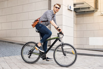 Fast vehicle. Smart handsome man riding a bike in the city while going to work in the office Wall mural