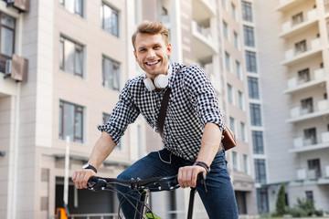 Healthy lifestyle. Joyful well built man smiling while enjoying the ride on the bike