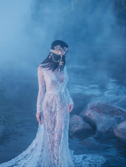 A nymph, walks in the middle of the river which has become dense, foggy. There is a white vintage dress. The girl turned her face away from the camera, a mysterious photograph of a stranger