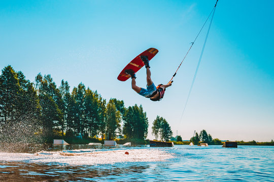 Young man wakeboarding on a lake, making raley, frontroll and jumping the kickers and sliders. Wakeboard.