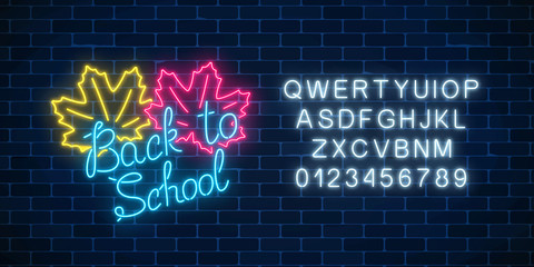 Neon banner with back to school greeting text and alphabet. Glowing neon sign with maple leaves. Welcome to school.