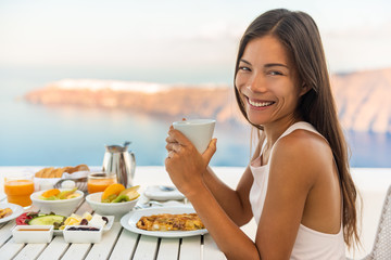 Wall Mural - Breakfast woman eating brunch at luxury travel hotel restaurant drinking coffee cup over Mediterranean view from outside balcony. Greek healthy food Santonini vacation.