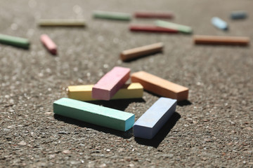 Many colorful chalk sticks on asphalt, closeup