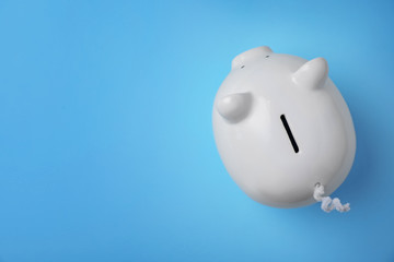 White piggy bank on color background, top view