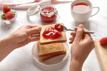 Woman spreading strawberry jam on toast bread over table