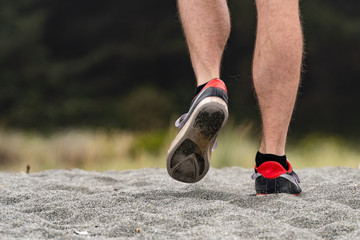 Male adult runs along a pacific coast sand beach with a shallow depth of field