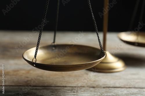 Scales of justice on wooden table against dark background