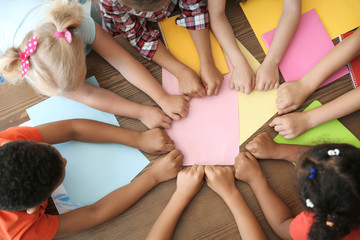 Little children putting their hands together at table, top view. Unity concept