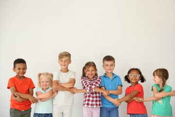 Little children holding hands on light background. Unity concept