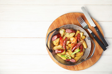 Pan with fried potatoes and sausages on wooden table, top view