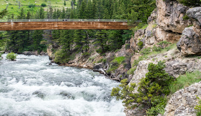 weathered wooden bridge overlooking the scenic Boulder River with it's rocky hillsides and lush forest near Big Timber, Montana