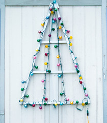 simple homemade wooden Christmas tree with colorful lightbulb ornaments on an exterior wall