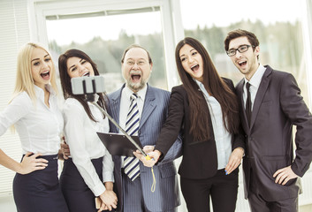 happy business team makes a selfie standing near the window in the office