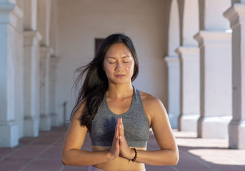 Athletic young woman practicing yoga outdoors, meditating with hands to heart and eyes closed