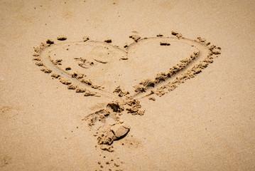 A heart shape made on a sandy beach.
