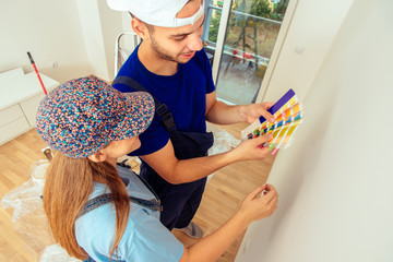 Young married couple choose color for wall in living room. Home renovation and improvement concept.