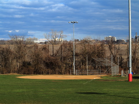Softball Field - Playing field with light towers and scenic blue sky and clouds.
