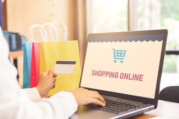 Woman hands paying online with a credit card and shopping online screen laptop. Colorful paper shopping bags are placed beside laptop.