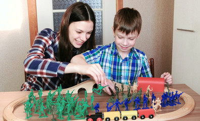 Playing together. Mom and son are playing a wooden railway with train, wagons and tunnel with plastic soldiers sitting at the table.