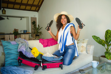 young attractive and crazy happy hispanic woman in beach Summer hat preparing suitcase leaving for holidays trip excited and messy about travel