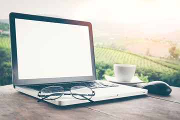 Eyeglasses on blank screen Laptop with coffee cup on wood table top at blur background of mountain. For Graphic display or montage your products.