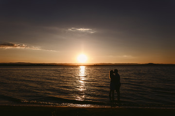 Silhouette couples in the sea at sunset
